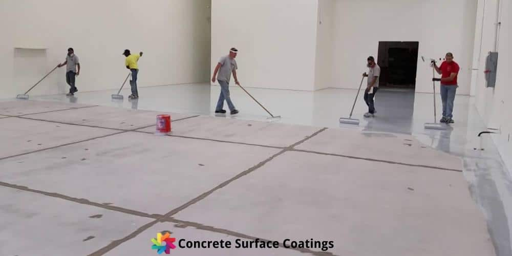 Concrete Surface Coatings staff applying an epoxy floor coating in a factory